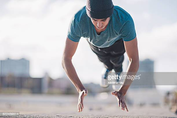 Athletic young man doing flying push ups