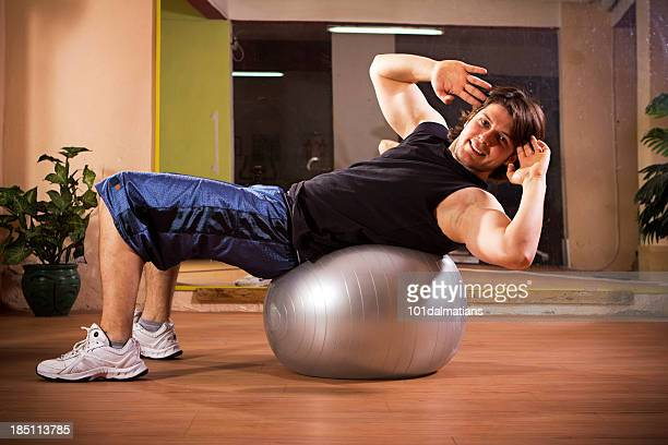Sportliche junge Mann Training auf pilates-ball