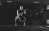 Athletic young man with battle rope doing exercise in the fitness gym. Sports concept.