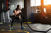 Athletic young woman doing gym exercises with a rope