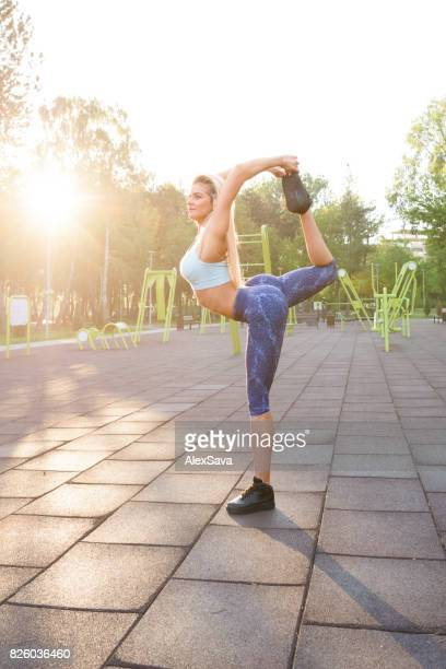 Athletic young woman stretching her body before calisthenics workout outdoor