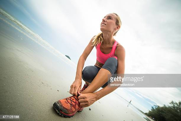 Athletic young woman tying shoes on the beach