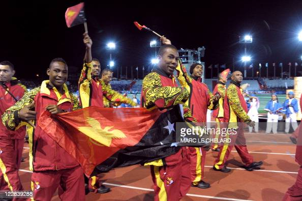 Athlets of the Papua New Guinea delegation wave flags as they attend the Opening Ceremony for the 14th Pacific Games on August 27 in the French South...
