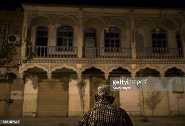 Athnic Uyghur man sits in the street on June 29 2017 in the old town of Kashgar in the far western Xinjiang province China Kashgar has long been...