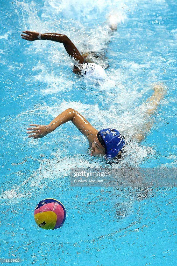 Athulya Meddegoda (top) of Sri Lanka and Neo Ser Han (bottom) of Singapore chase for the ball during the women Asian Water Polo Cup between Singapore and Sri Lanka at Toa Payoh Swimming Complex on October 5, 2013 in Singapore.