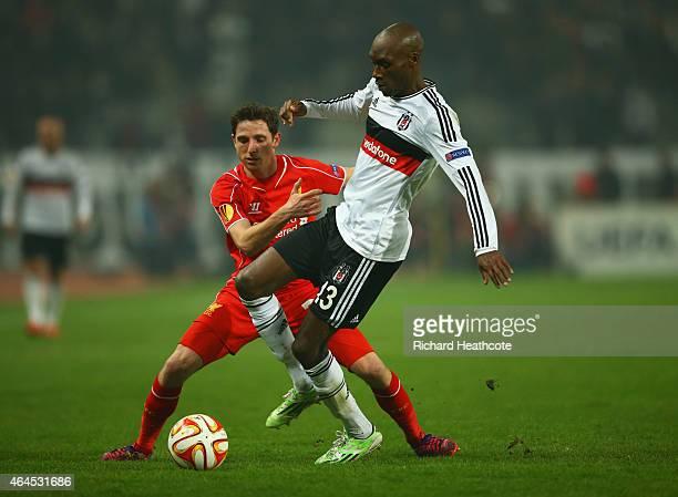 Atiba Hutchinson of Besiktas holds off Joe Allen of Liverpool during the UEFA Europa League Round of 32 second leg match between Besiktas JK and...
