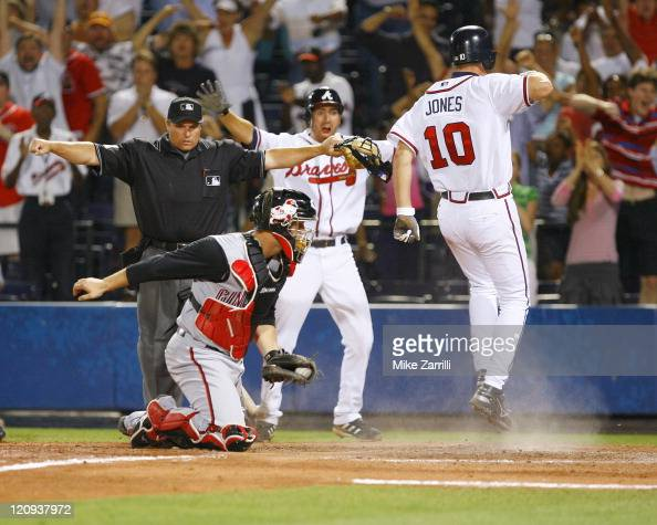 Atlanta Braves 3B Chipper Jones celebrates scoring the winning run in the bottom of the 10th inning during the game against the Cincinnati Reds at...