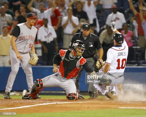 Atlanta Braves 3B Chipper Jones slides past Cincinnati Reds C David Ross in the bottom of the 10th inning during the game at Turner Field in Atlanta...