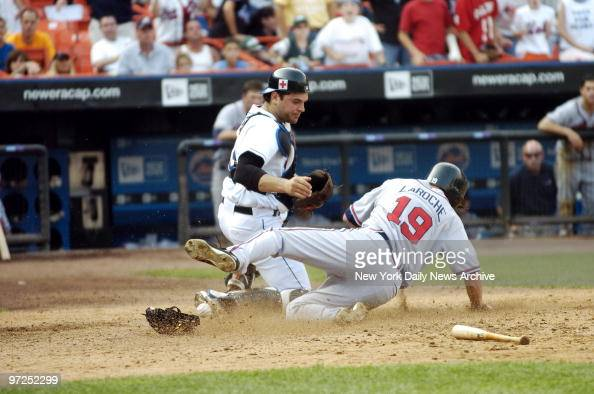 Atlanta Braves' Adam LaRoche slides in to score on a double by Ryan Langerhans as New York Mets' catcher Mike Piazza drops the ball in the ninth...