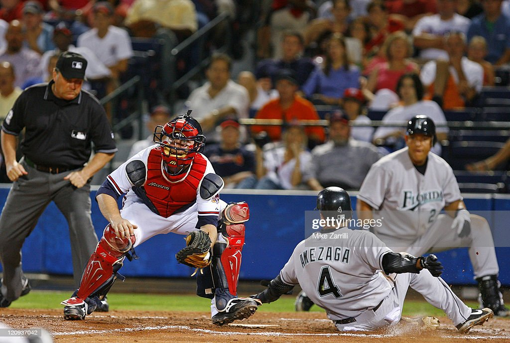 Atlanta Braves C <a gi-track='captionPersonalityLinkClicked' href=/galleries/search?phrase=Brian+McCann+-+Baseball+Player&family=editorial&specificpeople=593065 ng-click='$event.stopPropagation()'>Brian McCann</a> awaits a late throw from the outfield while Florida Marlins SS <a gi-track='captionPersonalityLinkClicked' href=/galleries/search?phrase=Alfredo+Amezaga&family=editorial&specificpeople=239472 ng-click='$event.stopPropagation()'>Alfredo Amezaga</a> slides home during the game between the Atlanta Braves and the Florida Marlins at Turner Field in Atlanta, GA on July 26, 2006. The Braves beat the Marlins 6-5.