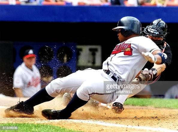 Atlanta Braves center fielder Andruw Jones is tagged out by New York Mets catcher Mike Piazza after attempting to score from first base on a hit by...