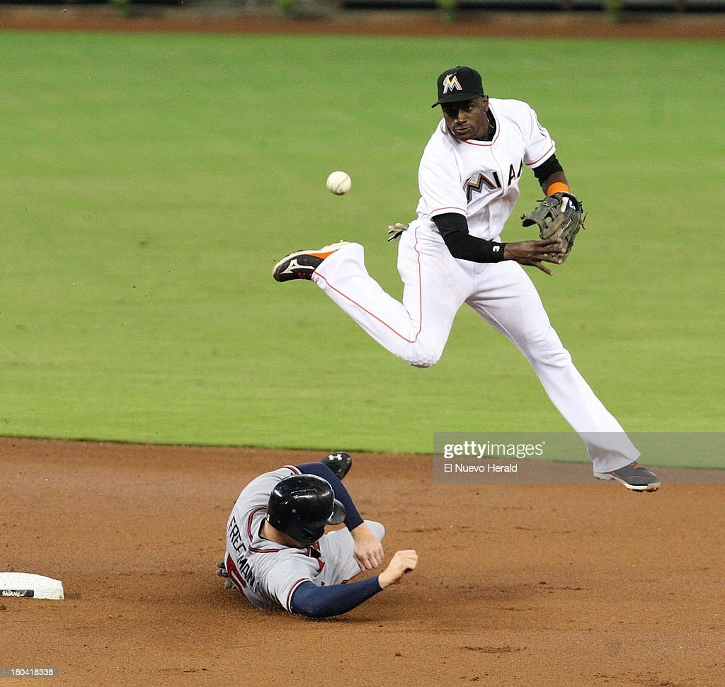Atlanta Braves' Freddie Freeman is out at second base, as Miami Marlins shortstop Adeiny Hechavarria completes a double play during the first inning at Marlins Park in Miami, Florida, Thursday, September 12, 2013.