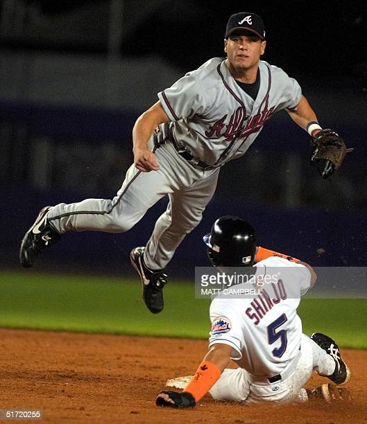Atlanta Braves second baseman Marcus Giles flys through the air after forcing out Tsuyoshi Shinjo at second and relaying to first for the double play...
