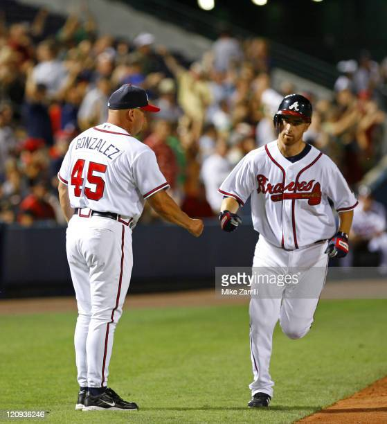 Atlanta Braves third base coach Fredi Gonzalez congratulates Braves 1B Adam Laroche after Laroche's game winning HR during the game between the...