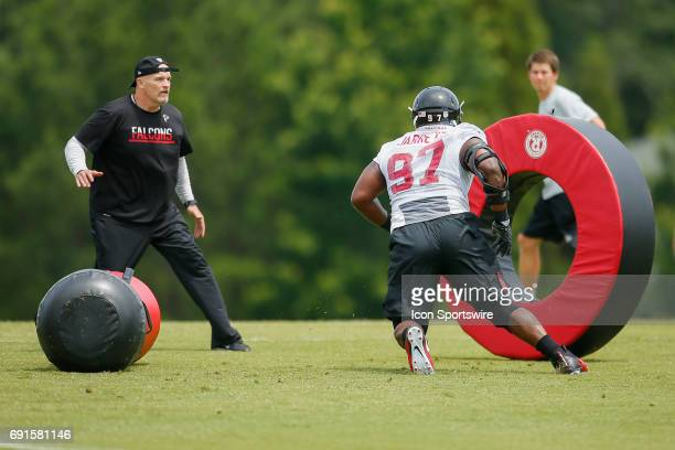 Atlanta Falcons head coach Dan Quinn watches on as defensive tackle Grady Jarrett takes part in a drill during a football practice in Flowery Branch...