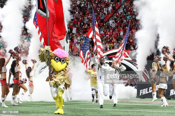 Atlanta Falcons mascot Freddie the Falcon and member of the military lead the team onto the field before the NFL game between the Miami Dolphins and...