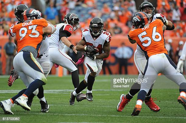 Atlanta Falcons running back Devonta Freeman eyes a big hole in the Denver Broncos defense after getting the handoff from Matt Ryan in the fourth...