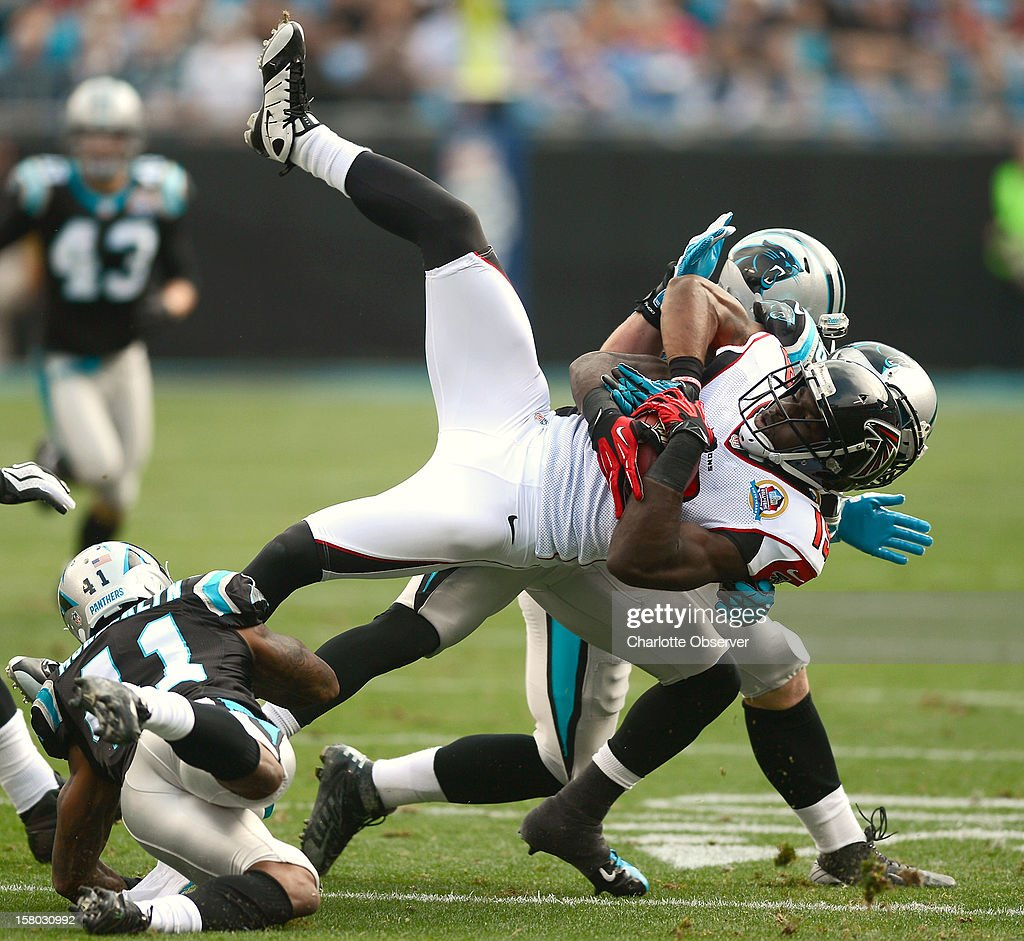 Atlanta Falcons wide receiver Drew Davis is upended by Carolina Panthers cornerback Captain Munnerlyn (41), safety D.J. Campbell (26) and linebacker Luke Kuechly (59) during first-quarter action at Bank of America Stadium on Sunday, December 9, 2012, in Charlotte, North Carolina.
