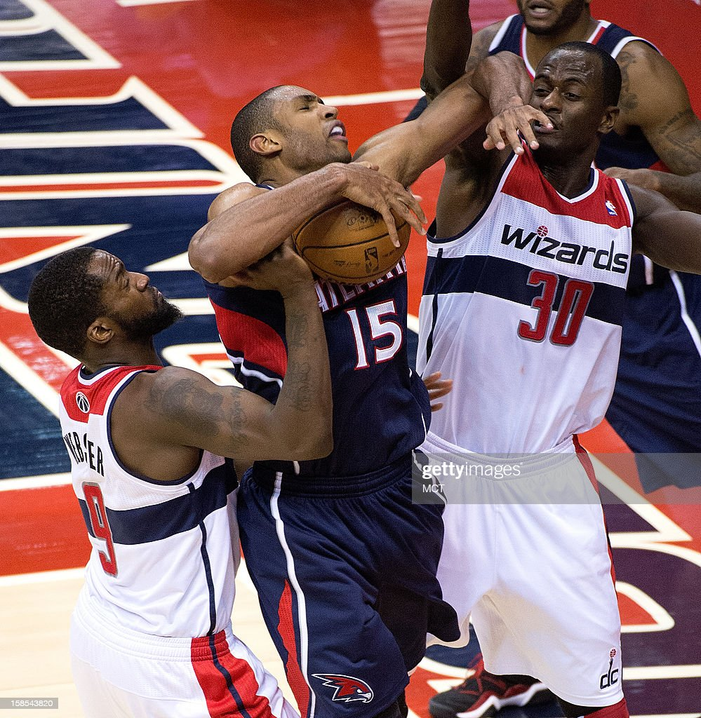 Atlanta Hawks center Al Horford (15) is fouled by Washington Wizards small forward Martell Webster (9), left and Washington Wizards center Earl Barron (30) during the overtime period of their game played at the Verizon Center in Washington, D.C., Tuesday, December 18, 2012. Atlanta defeated Washington 100-95 in overtime.