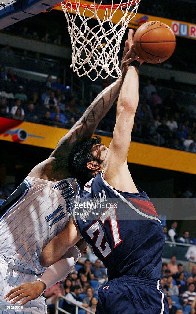 Atlanta Hawks center Zaza Pachulia (27) and Orlando Magic forward Glen Davis (11) battle for a rebound during an NBA game at the Amway Center on Wednesday, December 12, 2012. Atlanta won the game 86-80.