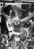 Atlanta Hawks player John Battle front center tries to dunk over Boston Celtics player Greg Kite back center at the Boston Garden in Boston during a...