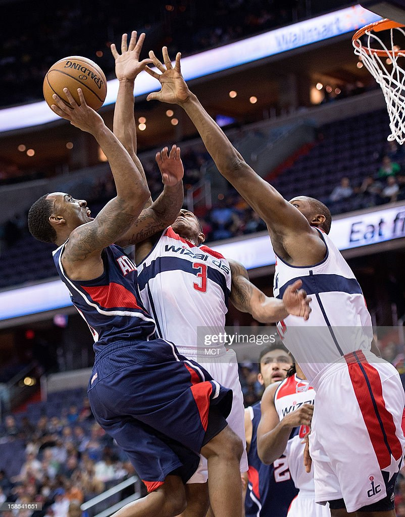 Atlanta Hawks point guard Jeff Teague (0) shoots over Washington Wizards shooting guard Bradley Beal (3) and power forward Kevin Seraphin (13), right, during the first half of their game played at the Verizon Center in Washington, D.C., Tuesday, December 18, 2012.
