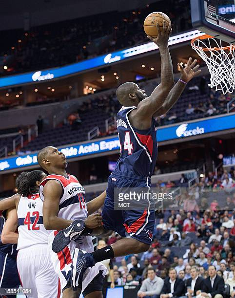 Atlanta Hawks power forward Ivan Johnson scores over Washington Wizards power forward Kevin Seraphin during the first half of their game played at...