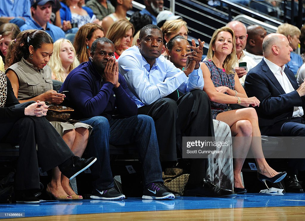 Atlanta Mayor Kasim Reed (dark blue) and former NBA star Dikembe Mutombo watch the action between the Atlanta Dream and the Connecticut Sun at Philips Arena on July 24, 2013 in Atlanta, Georgia.