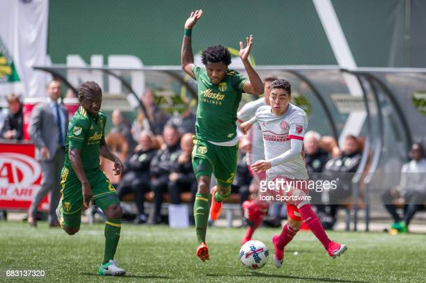 Atlanta United forward Miguel Almiron pushes forward marked by Portland Timbers defender Alvas Powell and midfielder Diego Chara on May 14 during the...