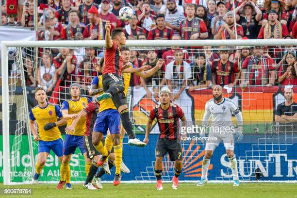 Atlanta's Brandon Vazquez heads the ball towards the goal as Josef Martinez and Tim Howard watch during a match between Atlanta United and the...