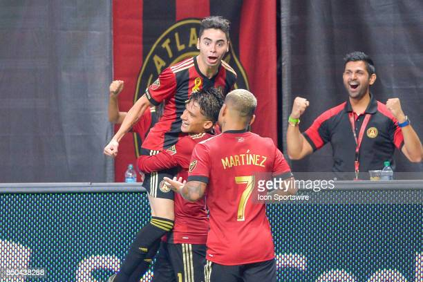 Atlanta's Miguel Almiron is congratulated by teammates Yamil Asad and Josef Martinez after scoring a goal during a match between Atlanta United and...