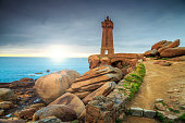 Stunning sunset with lighthouse of Ploumanach Mean Ruz in Perros-Guirec on Pink Granite Coast,Brittany,France,Europe