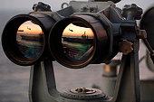 Atlantic Ocean, November 4, 2005 - The Nimitz-class aircraft carrier USS Dwight D. Eisenhower is reflected in a set of Big Eyes binoculars on the signal bridge of the Nimitz-class aircraft carrier USS Harry S. Truman.
