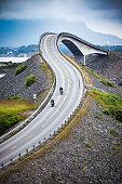 Two bikers on motorcycles. Atlantic Ocean Road or the Atlantic Road (Atlanterhavsveien) been awarded the title as 'Norwegian Construction of the Century'.