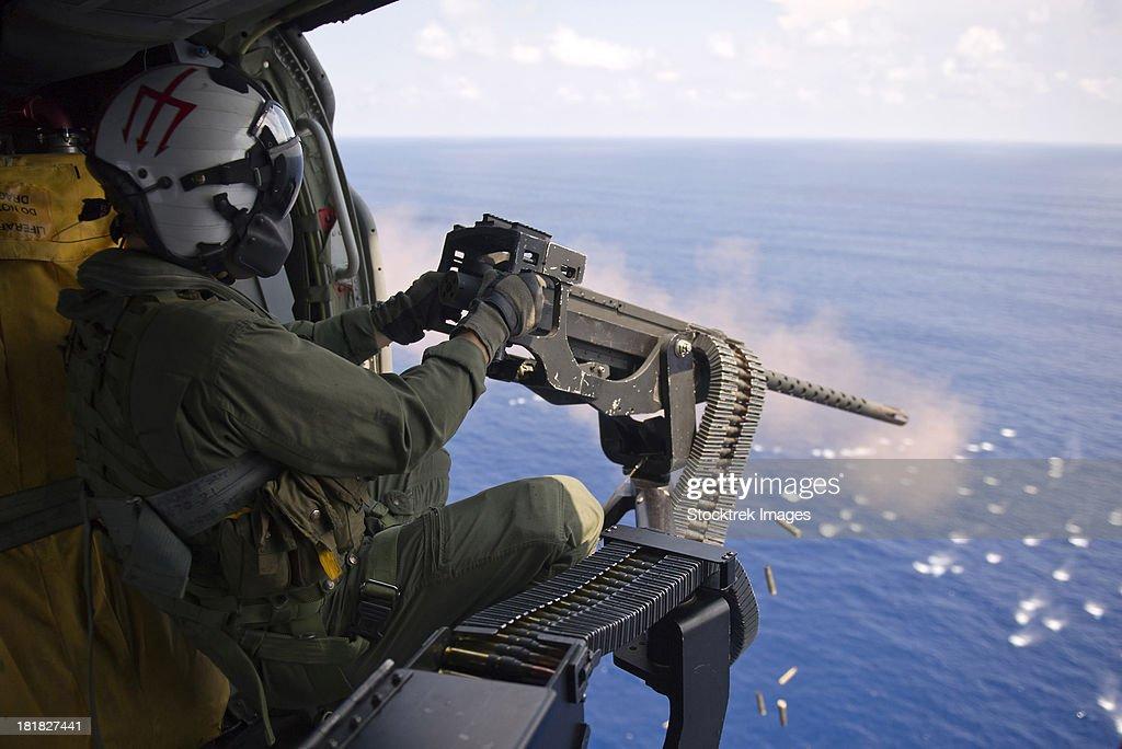Atlantic Ocean, September 6, 2012 - Naval Aircrewman in an MH-60S Knighthawk fires a .50-caliber machine gun at an MK-25 smoke target.