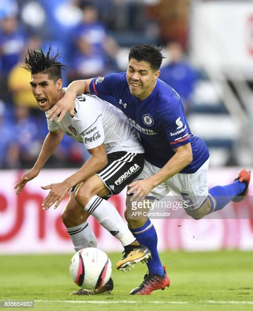 Atlas defender Jose Maduena vies for the ball with Cruz Azul defender Francisco Silva during their Mexican Apertura tournament football match at the...