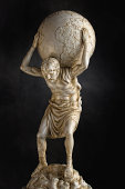 A resin statue replica of the titan Atlas of Greek mythology carries the weight of the heavens on his shoulders.  Dramatic lighting help accentuate the detail in the torso and legs.