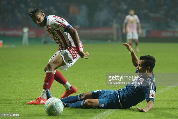 Atletico de Kolkata defender Keegan Pereira vies for the ball with FC Pune City midfielder Sanju Pradhan during the Indian Super League football...