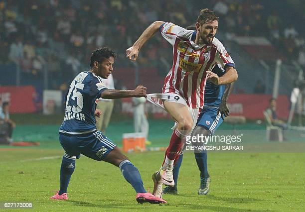 Atletico de Kolkata forward Juan Belencoso runs past FC Pune City defender Narayan Das during the Indian Super League football match between Atletico...