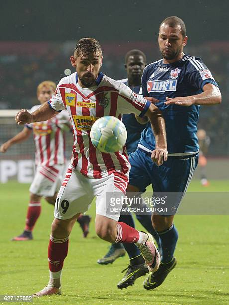 Atletico de Kolkata forward Juan Belencoso vies for the ball with FC Pune City defender Eduardo Ferreira during the Indian Super League football...