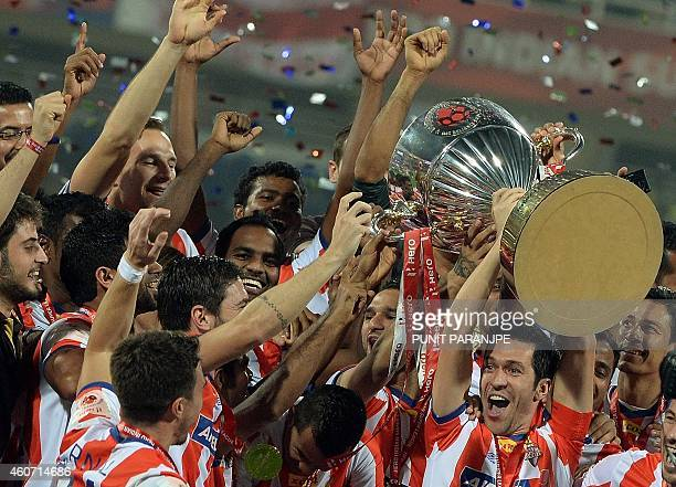 Atletico de Kolkata player Luis Garcia lifts the trophy as he celebrates with teammates after winning the Indian Super League final football match...