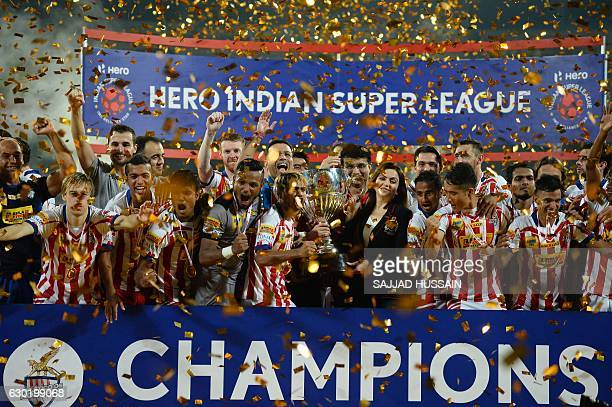 Atletico de Kolkata players celebrate with the trophy presented by Indian Super League director Nita Ambani after winning the ISL final football...