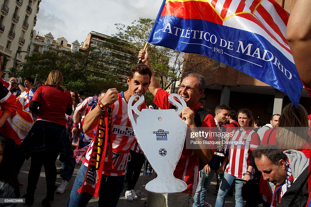 Atletico de Madrid fans cheer their team as they pose for a picture outside the Barclaycard Center before the UEFA Champions League Final match between Real Madrid CF and Club Atletico de Madrid on May 28, 2016 in Madrid, Spain. Real Madrid CF and Atletico de Madrid play the final match of the UEFA Champions League in Milan.