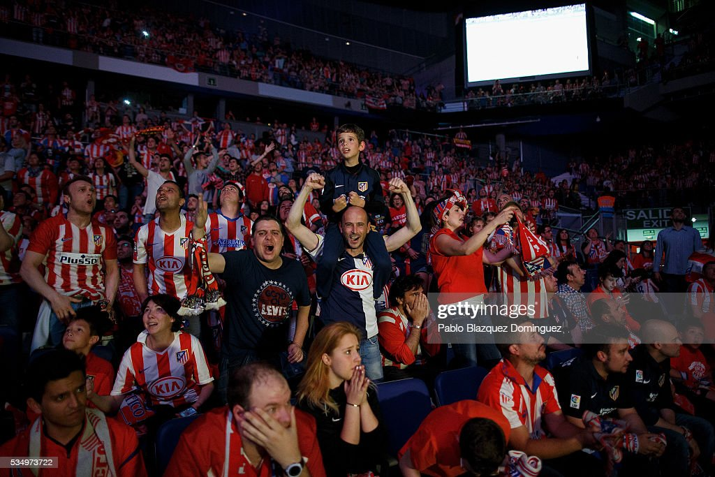 Atletico de Madrid fans react after their team scored its first goal as they watch the UEFA Champions League Final match between Real Madrid CF and Club Atletico de Madrid at Barclaycard Center before on May 28, 2016 in Madrid, Spain. Real Madrid and Atletico de Madrid play the final match of the UEFA Champions League in Milan.