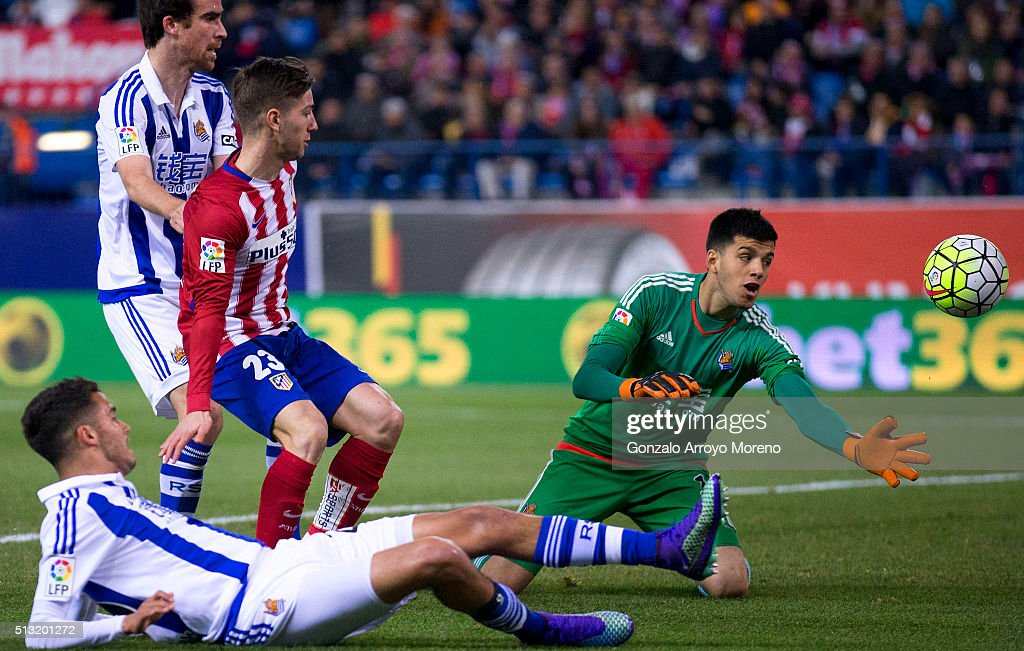 Atletico de Madrid scores their opening goal against goalkeeper Geronimo Rulli (R) of Real Sociedad de Futbol during the La Liga match between Club Atletico de Madrid and Real Sociedad de Futbol at Vicente Calderon Stadium on March 1, 2016 in Madrid, Spain.