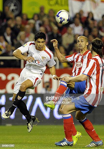Atletico de Madrid's Mariano Pernía vies for the ball with Sevilla's Renato Dirnei during their Spanish league football match at Sanchez Pizjuan...