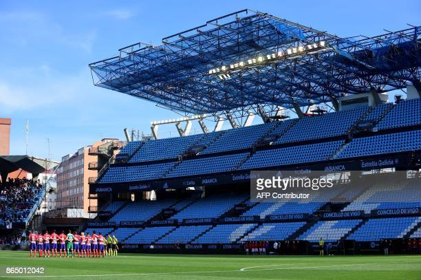 Atletico de Madrid's players observe a minute of silence in memory of the victims of wildfires next an empty grandstand closed for security reasons...