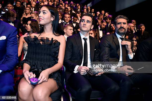 Atletico Madrid and France's forward Antoine Griezmann sits next to Georgina Rodriguez partner of Real Madrid and Portugal's forward Cristiano...