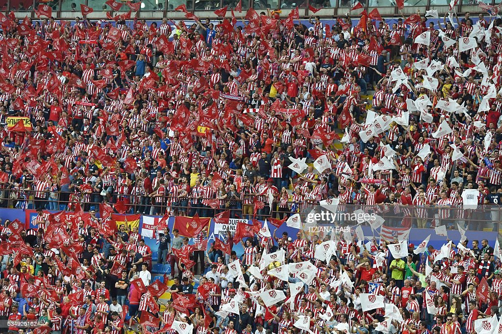Atletico Madrid (L) and Real Madrid supporters cheer and wave team flags ahead of the start of the UEFA Champions League final football match between Real Madrid and Atletico Madrid at San Siro Stadium in Milan, on May 28, 2016. / AFP / TIZIANA
