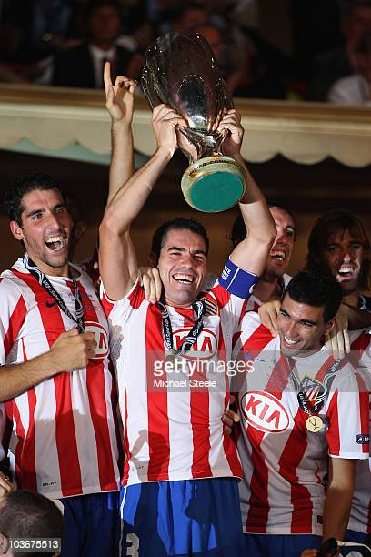 Atletico Madrid captain Antonio Lopez lifts the Super Cup alongside Raul Garcia and Jose Antonio Reyes after their 20 win during the UEFA Super Cup...